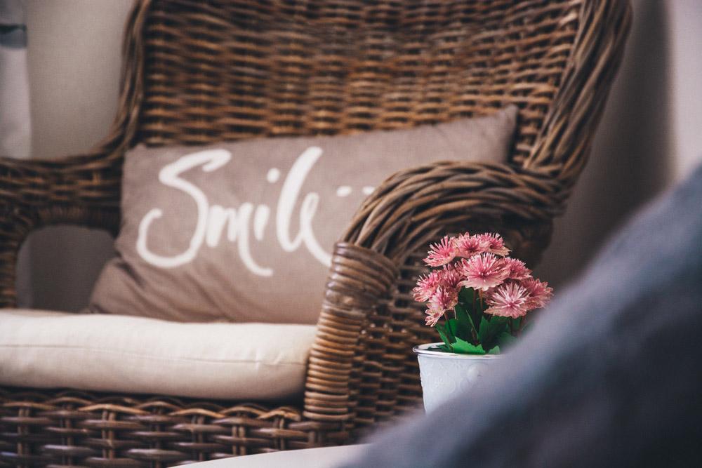 interior design trends wicker furniture and smile pillow